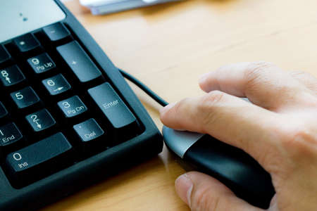 Human hand on computer mouse and keyboard Stock Photo - 24426369