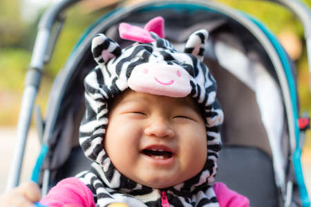 Happy young baby sitting in the baby carriage Stock Photo - 24655749