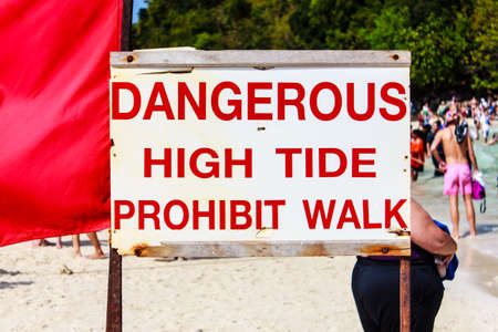 Beach sign that says, Dangerous High Tide Prohibit Walk. photo