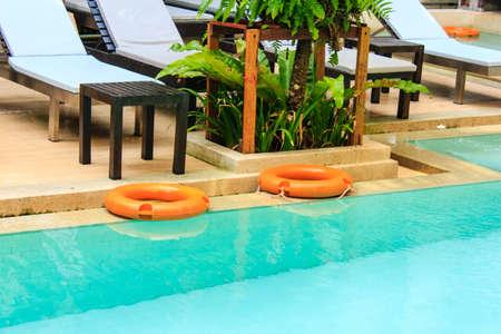 mandatariccio: orange lifebuoy with yellow ropes on tiled floor