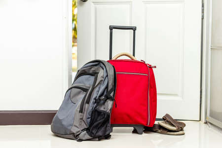 red travel bag , backpack and shoes by front door  版權商用圖片