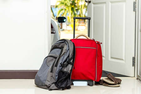 going: red travel bag , backpack and shoes by front door  Stock Photo