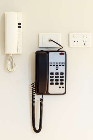intercommunication: intercom home & telephone hung on a white wal