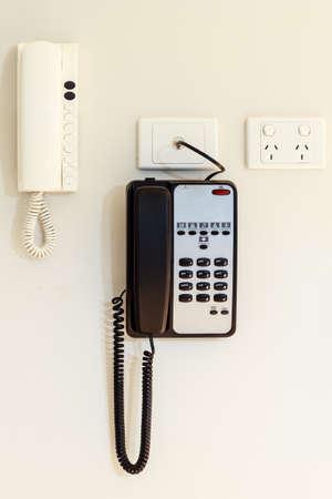 intercommunication: intercom home & telephone hung on a white wal