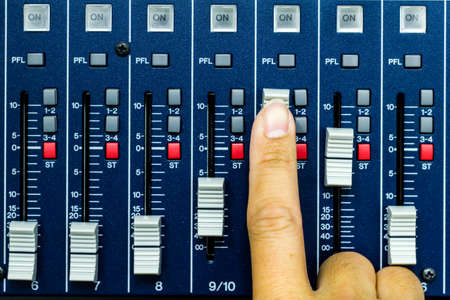 fader: Hand pushing open a fader on a sound desk