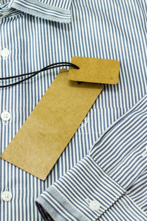 label tag: Brown tag label on white & blue shirt Stock Photo