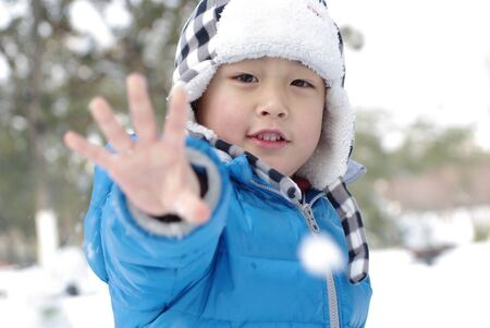 a boy is showing hand in winter photo