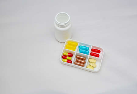 colorful capsules and pills with packaging on pure backround photo