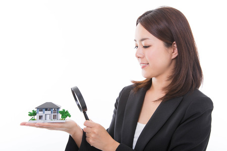 Career woman inspecting a house with magnifying glass. Real estate concept.