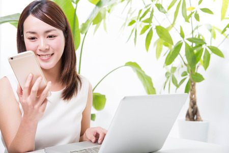 girl with laptop: Young woman with smartphone