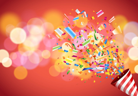 Exploding party popper on colorful defocused blurred background.