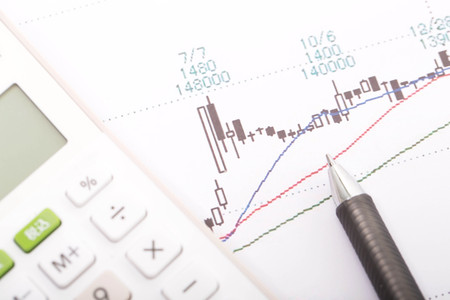 Stock market graph with calculator and pen Stock Photo