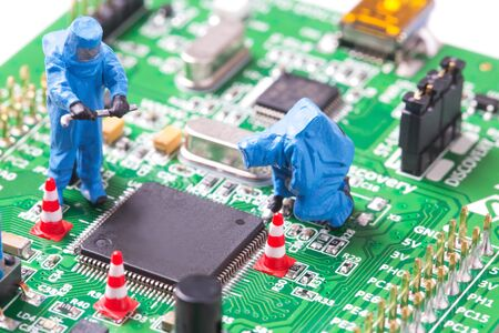 Miniature computer engineers working on a computer circuit board Stock Photo