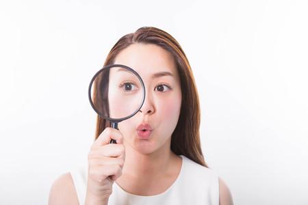 Jonge vrouw kijkt door een vergrootglas op een witte achtergrond