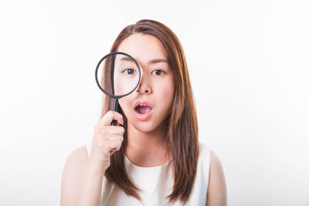 Young woman looking through a magnifying glass on a white background Фото со стока