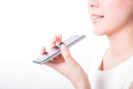 젊은 여자가 스마트 폰으로 음성 메시지를 녹음 스톡 콘텐츠