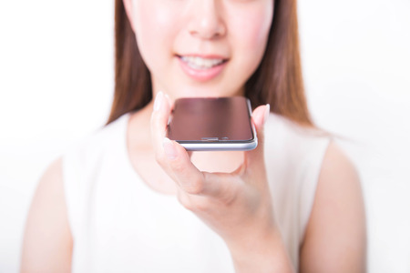 Young woman recording voice message with smartphone