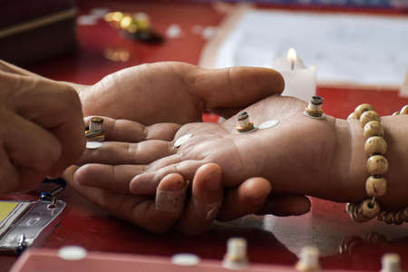 Close up of fortune teller with candles on the palm. Ancient healing