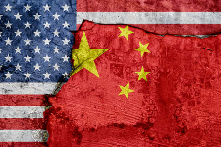 Flag of USA and China on cracked concrete wall background.