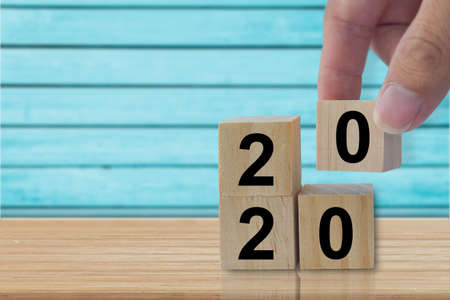 Design concept - Hand holding wood cubes with number 2020 and goal icon on wooden table. with copy space Standard-Bild - 142283988