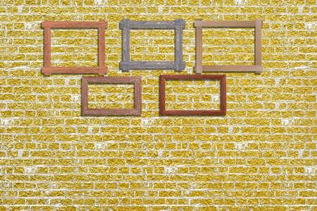 Vintage photo frames on golden brick wall for interior or background. Standard-Bild