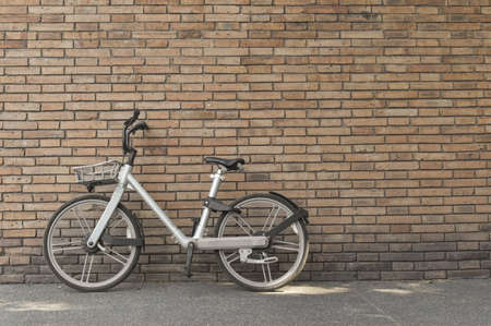 Retro bicycle on roadside with vintage brick wall background with copy space. Stockfoto