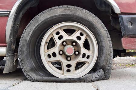 Abandoned car on the street. Flat tire and Tire burst Фото со стока