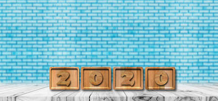 Word 2020 Alphabet letter wooden cube on wood table and blue brick wall background. With copy space for text
