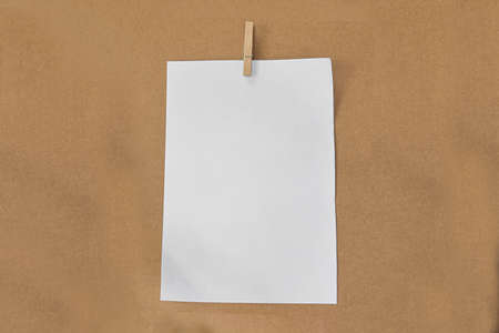 White paper and wood clip on brown paper background.