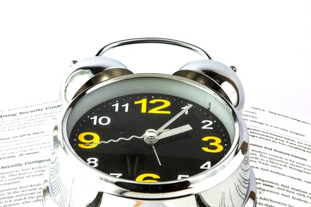 Silver alarm clock resting on a book Stock Photo