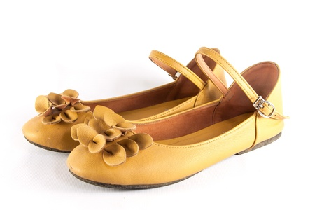 A pair of yellow shoes on white background