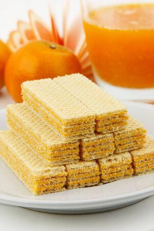Orange wafer on white dish with orange juice photo