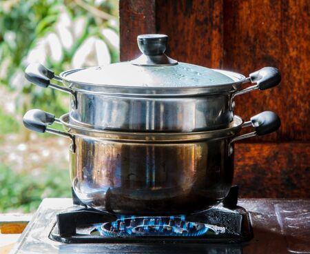 A pot  with many food cooking on gas