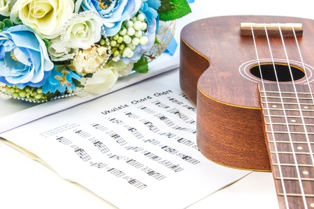 A classic ukulele,document and bunch of flower on white background Stock Photo
