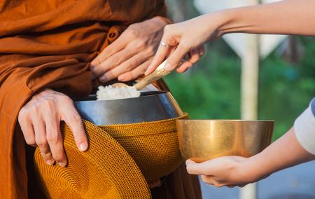 Femme aumône à un moine bouddhiste le matin