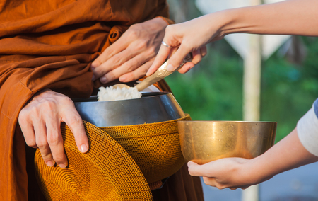Woman give alms to a Buddhist monk on morning
