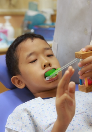Young boy  in dentel chair waiting for enamel fluoride gel application Stock Photo