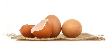 Fresh eggs and half of eggshell on white background