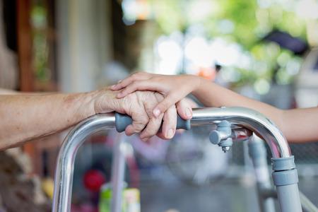 Jeune toucher la main vieille femme main qui tient Walker