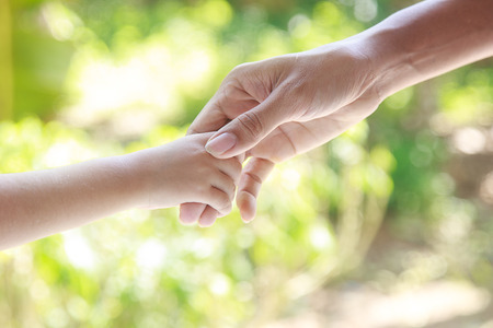 helping hand: Helping hands  - man holding child hand with love Stock Photo