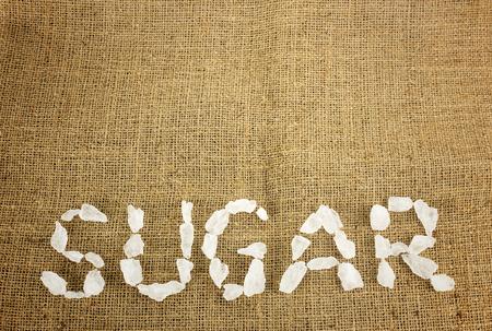 crystalline: White crystalline sugar arrange as word sugar  on brown hemp Stock Photo