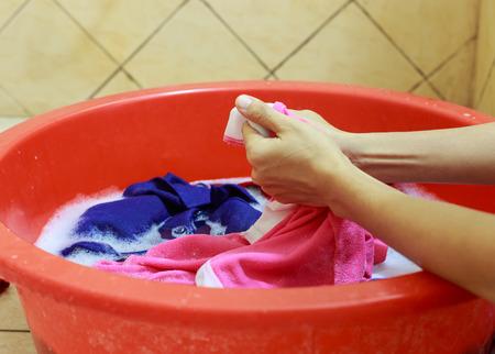 lavado: Dos manos lavando ropa en la tina roja