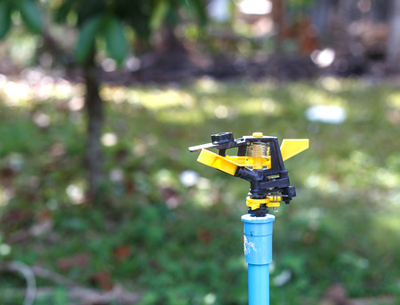 Sprinkler - water system in garden for plant and lawn Stock Photo