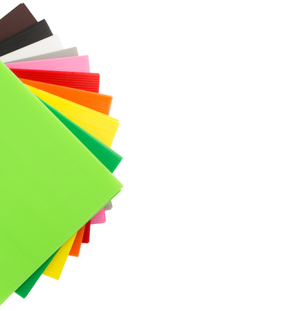 Stack of colorful  corrugated plastic sheets isolated on white