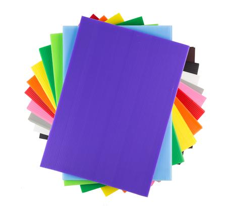 Pila de hojas de plástico corrugado de colores aislados en blanco