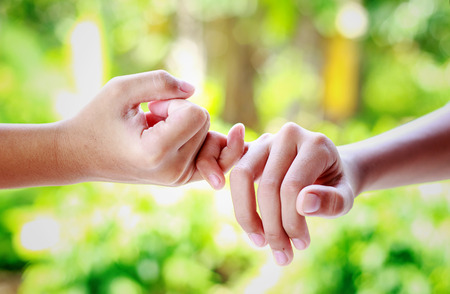 two people with others: Two hands hook each others little finger concept of promise Stock Photo