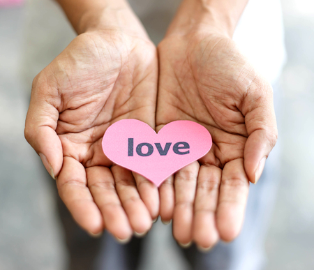 Colse up of hands holding heart pink card Stock Photo
