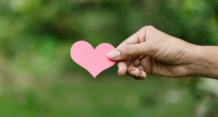 Hands holding pink heart paper against nature background