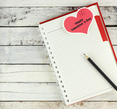 Red spiral notebook with happy valentines day card and pencil on white wood