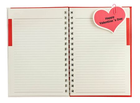 Red spiral notebook with happy valentines day card isolated on white